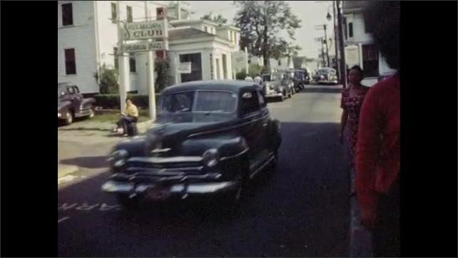 1940s: Cars, pedestrians pass along street in Cape Code village.
