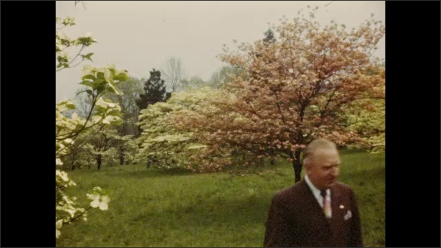 1940s: Man walks among flowering dogwood trees in Valley Forge National Historical Park; Automobiles drive past monument.