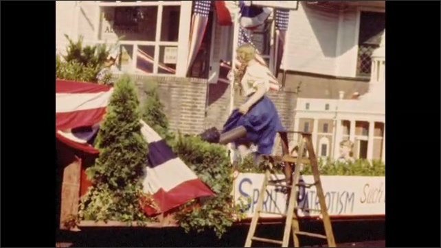 1940s: Costumed men and women board large float for 4th of July parade.