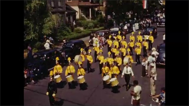 1940s: Marching band, majorettes, floats pass along residential street in 4th of July parade.