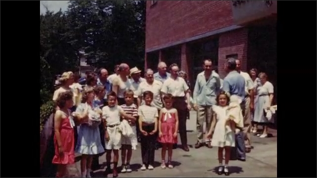 1940s: Group of people greet each other outside brick building.