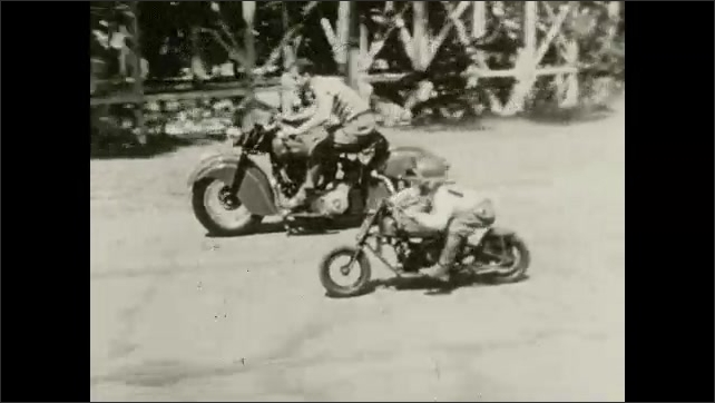 1950s: Man on motorcycle rides alongside small boy on miniature motorcycle.