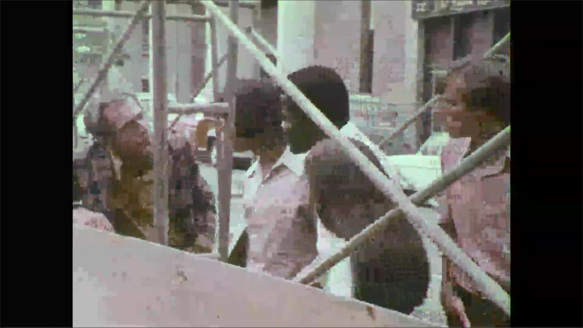Group of teenage 1970's students walk by construction site and stop to talk to an older man.