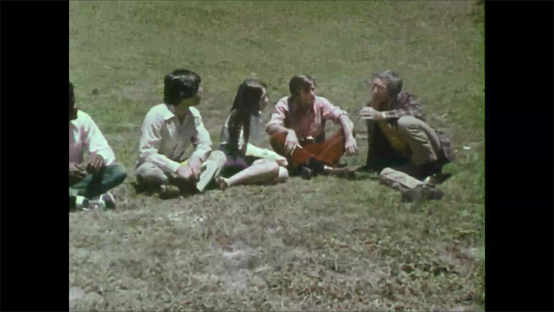 Group of 1970s students sits on grass listening to teacher.