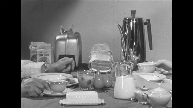 UNITED STATES 1950s: View of breakfast table, hands of man and woman drink coffee.