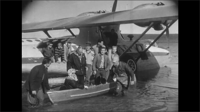 UNITED STATES 1950s: Man on boat holds onto seaplane / People exit seaplane on boat.
