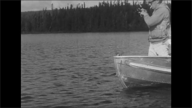 UNITED STATES 1950s: Man fishing on boat, pulls up fish.