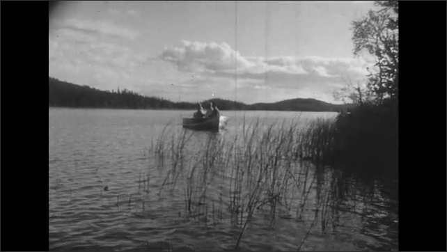 UNITED STATES 1950s: Long shot of men fishing in boat.