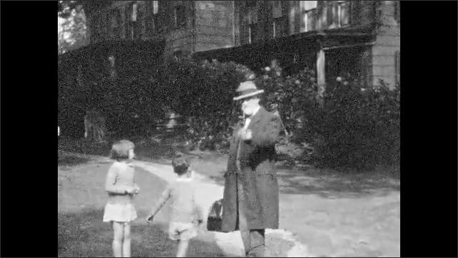 1930s: UNITED STATES: man walks along path to camera. Man smokes pipe. Children run towards man. Man and children look at camera.