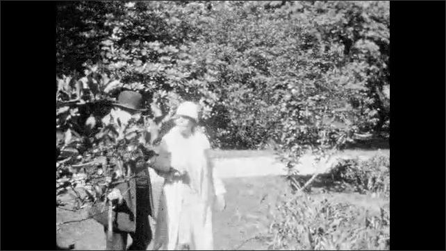 1930s: UNITED STATES: view through garden. Man and lady walk in garden.