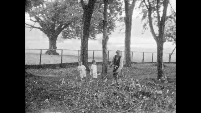 1930s: UNITED STATES: man carries branches from ground. Trees in gardens. Children watch man carry cut branches