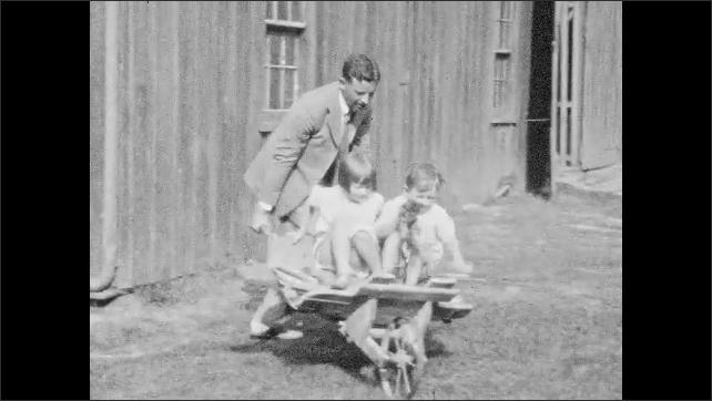 1930s: UNITED STATES: man helps children push wheelbarrow of wood. Children sit in wheelbarrow.