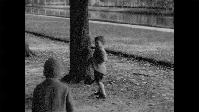 1930s: Boy and girl play with pet dog on long tree-lined road.