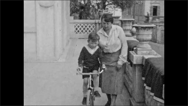 1930s: Girl holds cat on leash. Boy kneels next to dog in garden. Woman helps young boy ride bike on porch. Woman steadies and walks with boy on bicycle.