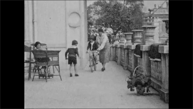 1930s: Woman holds bike steady for young boy. Woman walks with young girl on bike. Woman holds bike steady for young girl while boy walks nearby.