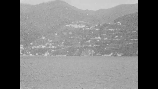 1930s: Homes and buildings dot hillside in mountain lake valley. Homes hug lake in mountain valley.