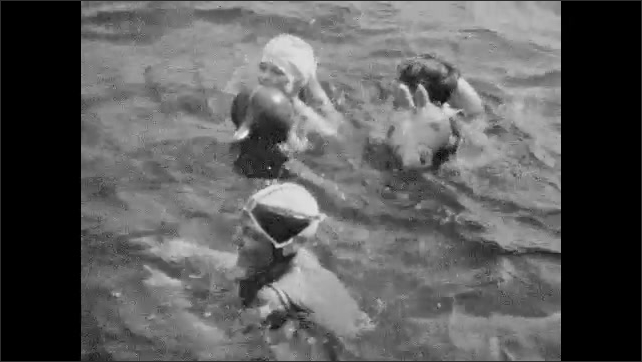 1930s: Woman and children with inflatables swim and play in water.