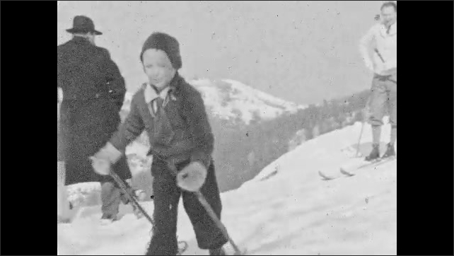 1930s: Family stand on top of snowy hill in ski gear. Boy walks across hill in skis. Girl walks across hill in skis.