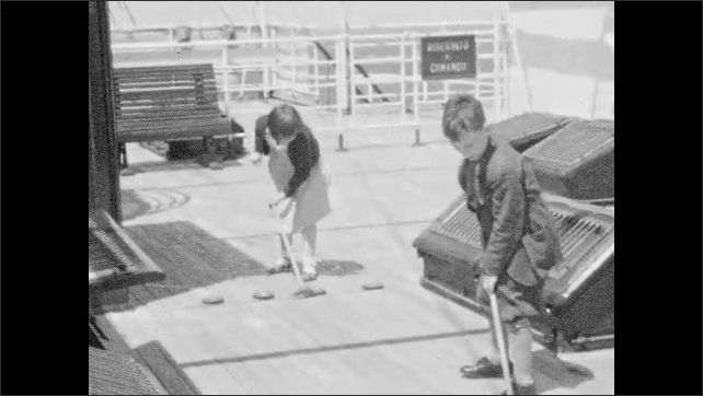 1930s: Boy watches girl putt golf ball. Boy and girl toss rings at horseshoe peg. Boy and girl play shuffleboard on boat deck.