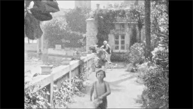 1930s: UNITED STATES: boy walks along path. Family walk back from swim. Lady and boy walk in gardens