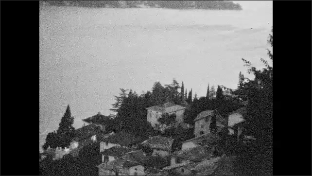 1930s: UNITED STATES: view from hill top down to village. View across lake towards mountains. Lake and shore.