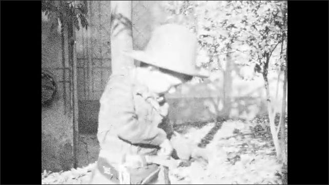 1930s: UNITED STATES: ladies stand with children in garden. Boy dressed as cowboy. Boy plays with toy gun. Boy makes pretend gun with fingers.