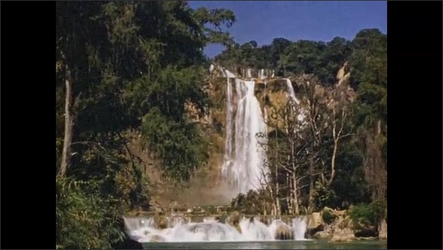 1940s: MEXICO: waterfall in park. Boy climbs up to tree. Lady pulls boy up to tree. Water in forest. Boy in water