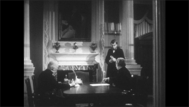1940s: 1800s reenactment. Civil War battlefield. Canons fire and Union troops charge. Inside, Abraham Lincoln consults with two men at a table.
