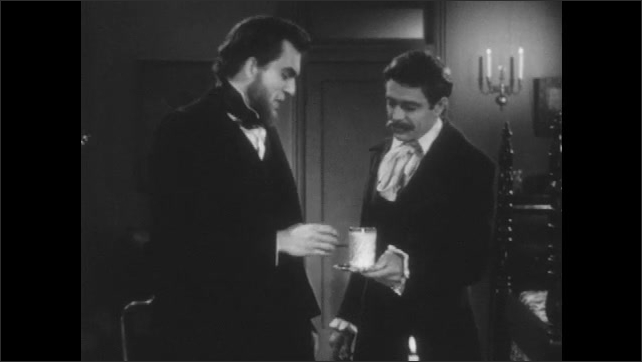 1940s: 1800s reenactment. A man offers a glass of milk to Abraham Lincoln as he sits at a desk. He stands and accepts it.