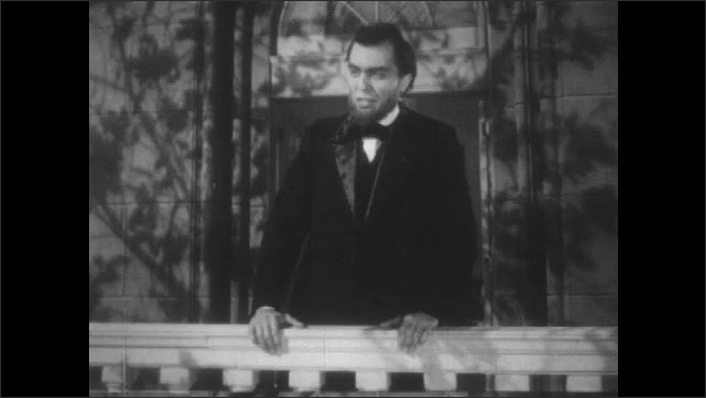 """1940s: 1800s reenactment. Abraham Lincoln delivers a speech from a balcony. Newspaper headline reads, """"Lincoln Assassinated."""""""