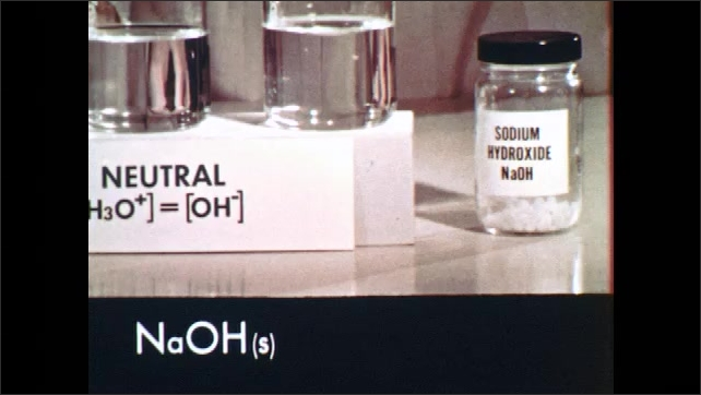 1960s: Man opens jar of sodium hydroxide, dumps crystal into beaker of liquid. Man stirs crystals into liquid. Chemical compound formula on screen. Man places label marked bsic in front of beaker.
