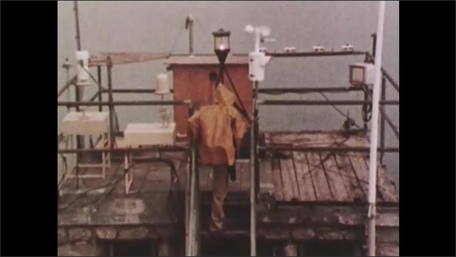 1970s: Man on top of building turns crank which raises device up, while man climbs onto roof of building and approaches weather device.