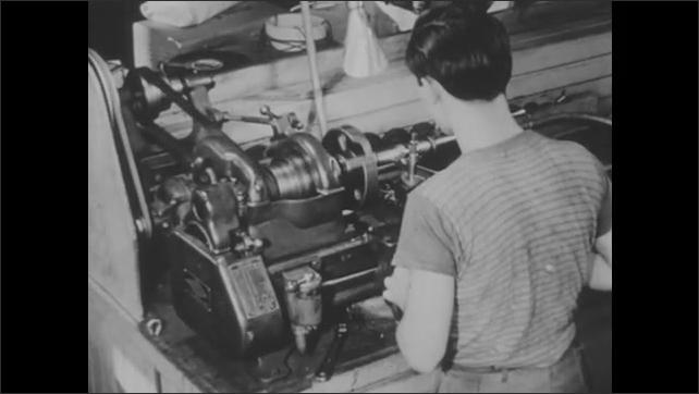 1940s: UNITED STATES: man uses lathe. Motor in operation on lathe.