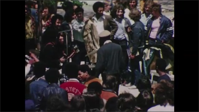 1970s: Students gather outdoors at arts event. Students line up at pools. Students raise hands in classroom.