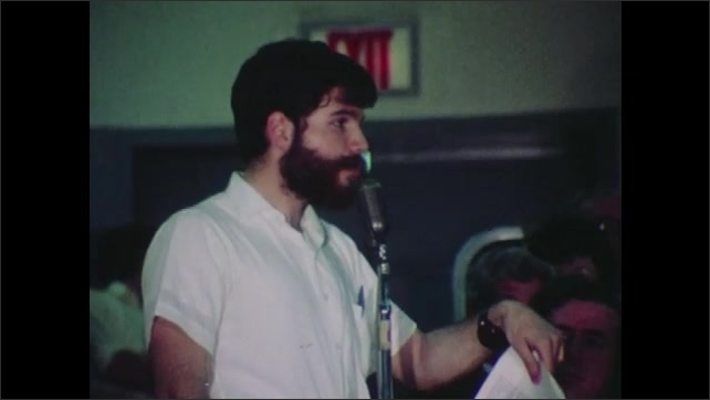 1970s: Young man and woman speak. Man speaks into microphone and gestures. Woman writes.