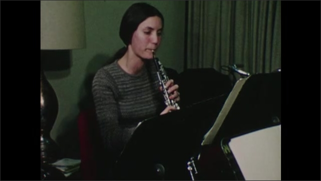 1970s: Man playing clarinet, pan to woman playing oboe. Woman playing clarinet, pan to woman playing flute. Man playing French horn.