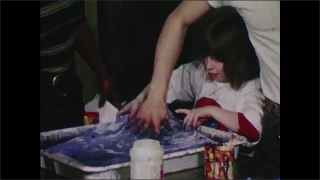 1970s: Man and girl put paper in water, flip paper. closee up, girl looks at paper.