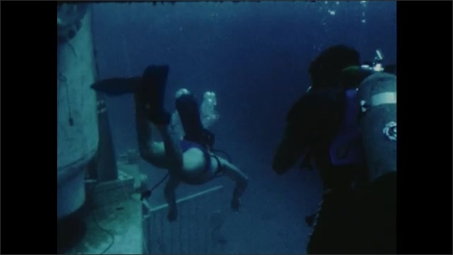 1970s: Divers swimming by tank. People around table look at papers.