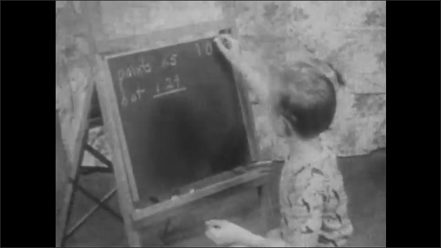 1940s: Boy writes value of objects on chalkboard in living room. Boy smiles. Boy writes numbers on chalkboard.
