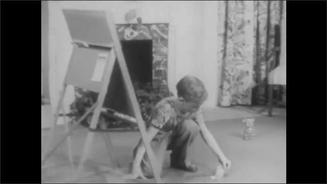 1940s: Boy writes numbers on chalkboard in living room. Boy stops. Boy sets out change and cash on living room for and begins separating it out.