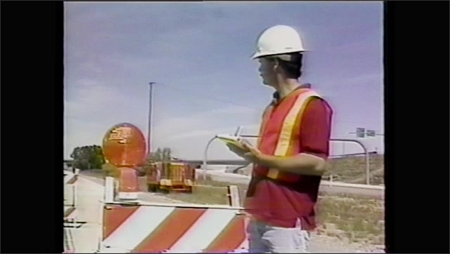 1990s: Orange traffic cones. Orange barrels. Orange and white traffic barricades. Construction worker makes notes and measures distance between barriers.