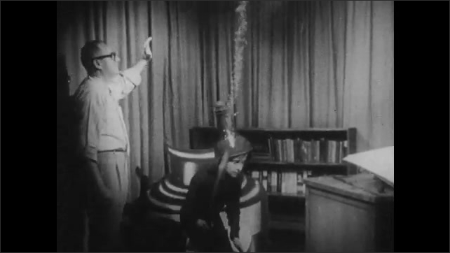 1960s: Man gets up from desk, removes lid from cartoon display bottle of ink. Child dressed up in costume jumps out of display, sits on desk and shows paper to man.