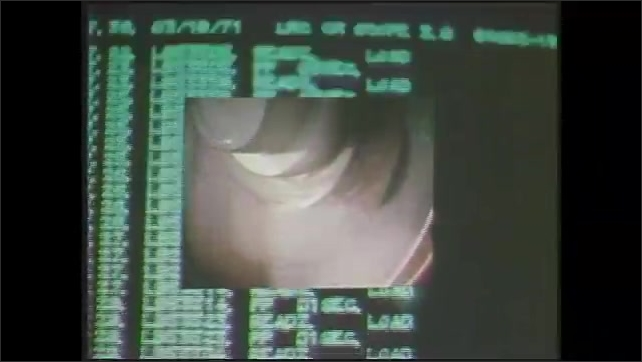 1970s: Text on computer screen, picture-in-picture, zoom in on wires. Tape reels turning. Close up of man. Tape reels turning.
