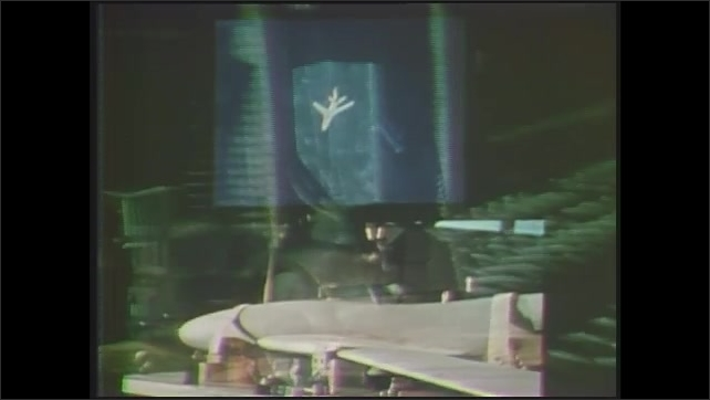 1970s: Split screen, jet flying, body of jet rotating. Machine parts moving. Parts moving, man in window in background. Parts moving, computer graphics superimposed over image.