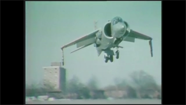 1970s: Pan from plane to men working. Jet in hangar. Close up of man, pan to hand on steering wheel. Jet landing. Split screen of planes, runways. Jet flying. Men in cockpit.