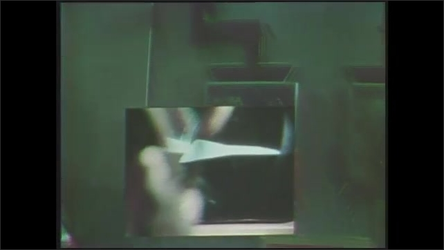 1970s: Picture-in-picture, pan across computer consoles, models of jets. Close up of men. Hand turns knobs, machine parts moving. View of jet model, zoom in on light.