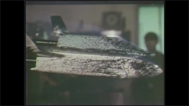 1970s: Aerial view of jet lowering over land. Model of space shuttle. Picture-in-picture, views of shuttle model. Animation of rocket over lights, text on computer screen.
