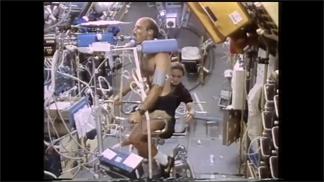 1990s: Person floats through interior of Space Shuttle where other astronauts are doing things. Astronauts exercise, vitals are taken. Astronaut writes down information.
