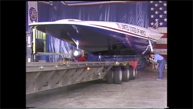 1990s: Truck trailer is backed into warehouse, underneath experimental airplane. Plane is hauled down road on back of truck bed.
