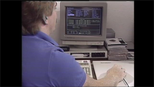 1990s: Men sit in office, look at computer screen images of fields.